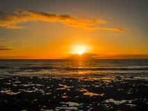 与云彩的五颜六色的日落由海洋 免版税库存图片