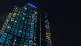 与云彩的夜空在有发光的窗口建筑学timelapse的现代摩天大楼上 股票录像