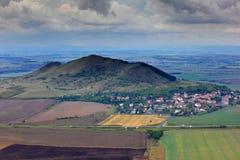 与云彩的小山 美好的横向早晨 在小山下的村庄 与领域和草甸的风景在土墩附近 以前天空 免版税库存照片
