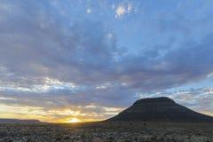 与云彩的日落在南部非洲的干旱台地高原 库存图片