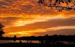 与云彩的日落,在橙色和紫色树荫下 免版税库存照片