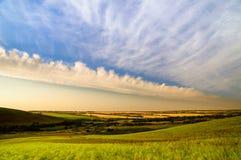 与云彩的美丽的天空在多小山乡下 库存照片