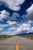 与云彩的蓝天在沙漠和路 免版税库存照片