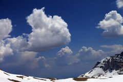 与云彩的蓝天在雪山 库存图片