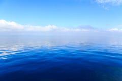 与云彩的蓝色海洋水在背景中 免版税库存图片