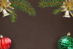 与云杉、圣诞节装饰响铃,红色波浪和绿色球分支的黑暗的背景  免版税图库摄影