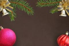 与云杉分支,圣诞节装饰响铃,桃红色,红色波浪球的黑暗的背景 库存图片