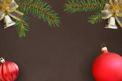 与云杉分支,圣诞节装饰响铃,红色波浪愚钝的球的黑暗的背景 免版税图库摄影