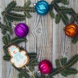 与云杉的分支和圣诞节树球框架的轻的木破旧的背景  免版税库存图片