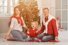 与五彩纸屑的愉快的家庭在圣诞树背景与 免版税库存照片