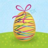 与五颜六色的丝带的大黄色复活节彩蛋 库存图片