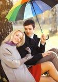与五颜六色的伞一起的愉快的年轻夫妇在秋天 库存照片