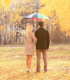 与五颜六色的伞一起的年轻夫妇在温暖的晴朗的秋天天观看  免版税库存照片