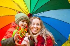 与五颜六色的伞的愉快的家庭在秋天公园 免版税库存图片
