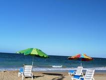 与五颜六色的伞的海滩睡椅 免版税库存照片