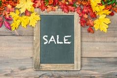 与五颜六色的叶子和黑板的秋天背景 销售额 免版税图库摄影