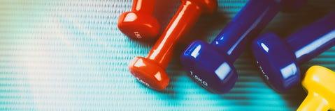 与五颜六色的哑铃的健身背景 健康生活方式co 免版税库存照片