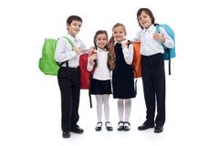 与五颜六色的回到装箱的愉快的小学孩子 免版税库存图片