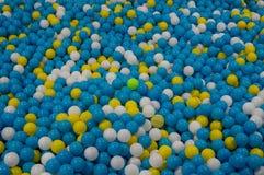 与五颜六色的塑料球的背景,它是孩子的玩具,也是 免版税库存照片