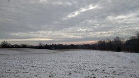 与五颜六色的多云天空的积雪的领域 免版税库存图片