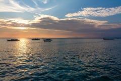 与五颜六色的天空和小船的日落在海 免版税库存照片