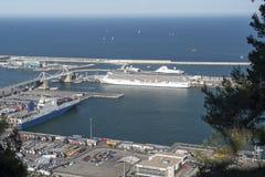 与五颜六色的容器和一艘大白色船的货物口岸 图库摄影