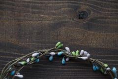 与五颜六色的小珠的圆的花圈在黑褐色木背景,平的位置,拷贝空间 免版税库存照片