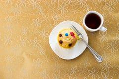 与五颜六色的巧克力片和一个杯子的松饼红茶 背景欢乐金黄 在视图之上 免版税库存照片