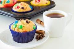 与五颜六色的巧克力片的自创松饼在深蓝纸箱和一个杯子红茶 奶油被装载的饼干 正面图 库存图片