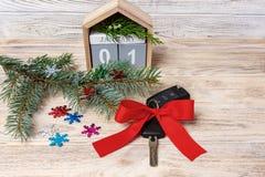 与五颜六色的弓和日历,圣诞树,分支,雪花的汽车钥匙,在木背景 免版税库存图片