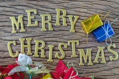 与五颜六色的当前箱子的金黄字母表圣诞快乐在wo 库存照片