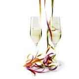 与五颜六色的彩纸带的两块长笛香槟玻璃在whi 图库摄影