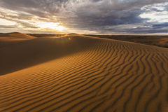 与五颜六色的日落的美好的沙漠风景 免版税库存照片
