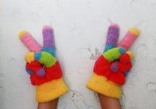 与五颜六色的条纹的被编织的儿童` s手套 免版税库存图片