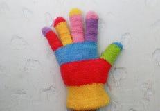 与五颜六色的条纹的被编织的儿童` s手套 免版税库存照片