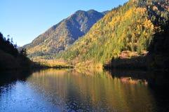 与五颜六色的条纹(反射)的山在湖 免版税库存照片