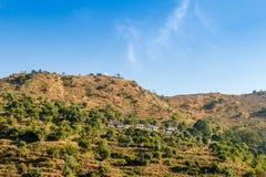 与五颜六色的森林和蓝天的庄严早晨山风景 小屋和绿色树在印地安人喜马拉雅山 库存照片