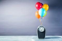与五颜六色的气球的体重计 减肥概念 免版税库存照片