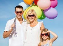 与五颜六色的气球的家庭 库存照片