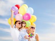 与五颜六色的气球的家庭 免版税库存图片