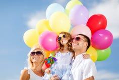 与五颜六色的气球的家庭 库存图片