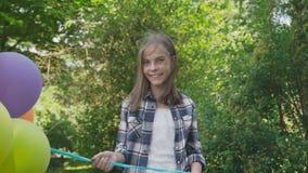 与五颜六色的气球的愉快的女孩欣喜在公园 影视素材