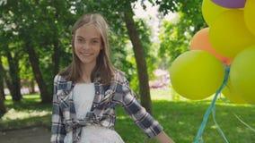 与五颜六色的气球的愉快的女孩欣喜在公园 4K 影视素材
