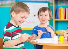 画与五颜六色的油漆的逗人喜爱的孩子在幼儿园 免版税库存照片