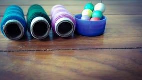 与五颜六色的泡影的五颜六色的缝合针线在木背景 库存照片