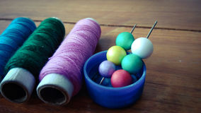 与五颜六色的泡影的五颜六色的缝合针线在木背景 库存图片