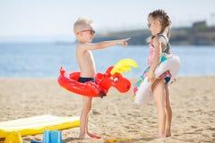 与五颜六色的浮体的滑稽的孩子在海滩 免版税库存照片