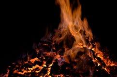 与五颜六色的火焰的美丽的炽热炙热的余烬堆在冬天夜 免版税库存图片