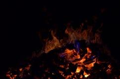 与五颜六色的火焰的美丽的炽热炙热的余烬堆在冬天夜 免版税图库摄影