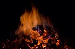 与五颜六色的火焰的美丽的炽热炙热的余烬堆 免版税库存照片